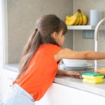 cute little girl washing dish kitchen by herself child reaching kitchen sink faucet tap turning water 74855 8029