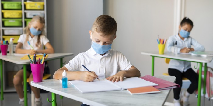 kids writing classroom while wearing medical masks
